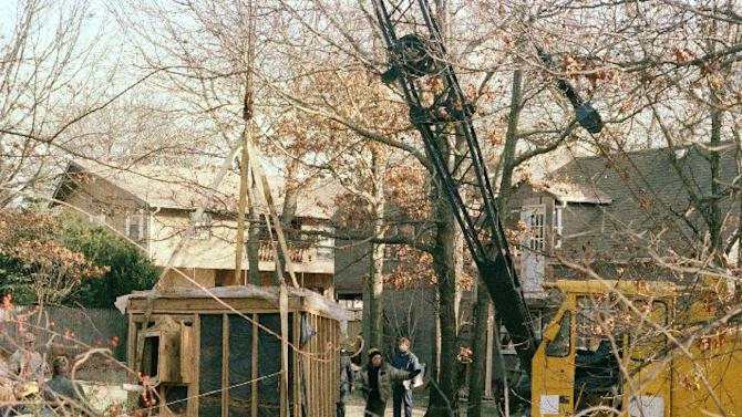 """FILE - In this Jan. 18, 1993 file photo, a crane raises a 6 foot by 9 foot bunker out of the earth from the property of John Esposito in Bay Shore, N.Y. Esposito kept 10-year-old Katie Beers imprisoned for 17 days in the cement and wood bunker, which contains a trap door. On the 20th anniversary of her ordeal, Beers has co-written a book with a television reporter who covered her kidnapping. """"Buried Memories: Katie Beers' Story"""" (Title Town Publishing) has a happy ending. (AP Photo/Michael Alexander, File)"""