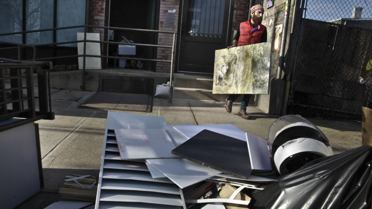 John Gordon Gauld, an artist who lost paintings during superstorm Sandy, moves a painting out of his Red Hook studio on Monday, Dec. 3, 2012 in New York.  (AP Photo/Bebeto Matthews)