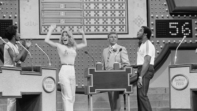 "FILE - In this June 25, 1980 file photo, as host Richard Dawson, center, watches, Dallas Cowboys running back Tony Dorsett, right, grimaces and Cowboys cheerleader Suzette Scholz-Derrick waves happily after Suzette beat Dorsett with a correct answer during taping of the ""Family Feud"" game show at ABC television studios in Los Angeles. Five Cowboys footballers meet five Cowboys cheerleaders for week of competition on the popular daytime game show. Dawson, the wisecracking British entertainer who was among the schemers in the 1960s sitcom ""Hogan's Heroes"" and a decade later began kissing thousands of female contestants as host of the game show ""Family Feud"" died Saturday, June 2, 2012. He was 79. (AP Photo/Randy Rasmussen, File)"