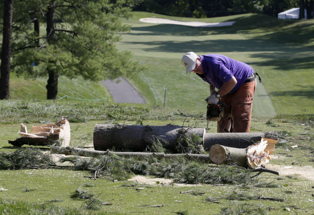 A worker chainsaws a tree that fell onto a tee box on the the 12th hole at Congressional Country Club in Bethesda, Md., Saturday, June 30, 2012, after a strong storm blew through overnight. The AT&amp;T N