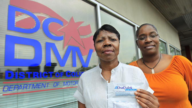 In this photo taken July 8, 2011, Sheila Brockington, project director of Family and Medical Counseling Service, Inc., left, and Deputy Director Angela Wood hold a swab kit outside the Department of Motor Vehicles (DMV) office in southeast Washington.  At one office of the Department of Motor Vehicles in the U.S. capital, motorists can get a driver's license, temporary road tax stickers and something wholly unrelated to the road: a free HIV test. (AP Photo/Manuel Balce Ceneta)