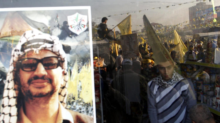 The image of late Palestinian President Yasser Arafat is displayed while Palestinians are reflected on the glass of a shop window during celebrations marking the 48th anniversary of the Fatah movement in Gaza City, Friday, Jan. 4, 2013. The secular-leaning Fatah party staged a massive rally Friday in the Gaza Strip, the first such gathering in the territory since the Islamist Hamas group violently took control there in 2007 - a reflection of the warming ties between the two rival Palestinian factions.(AP Photo/Hatem Moussa)