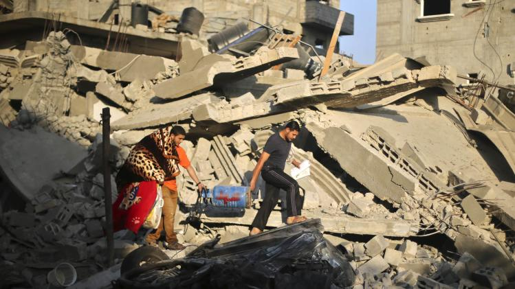 Palestinians carry their belongings from a house which police said was destroyed in an Israeli air strike in the northern Gaza Strip