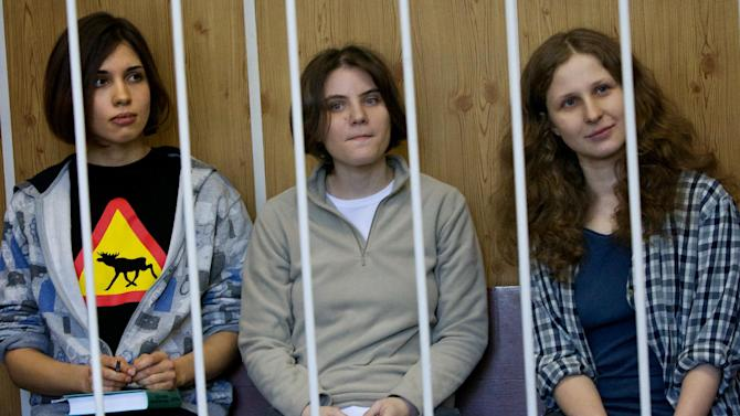 """From left, Nadezhda Tolokonnikova, Maria Alekhina, Yekaterina Samutsevich members of feminist punk group Pussy Riot sit behind bars at  a court room in Moscow, Russia, Monday, July 23, 2012.The trial of feminist punk rockers who chanted a """"punk prayer"""" against President Vladimir Putin from a pulpit inside Russia's largest cathedral started in Moscow on Friday amid controversy over the prank that divided devout believers, Kremlin critics and ordinary Russians. (AP Photo/Alexander Zemlianichenko)"""