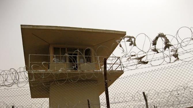 FILE - This Saturday, July 24, 2010 fil;e photo shows a guard tower and fences with barbed wire for a U.S.-funded prison in Khan Bani Saad, Iraq, northeast of Baghdad. This site is among hundreds of projects funded by U.S. taxpayers that remain abandoned or incomplete, wasting more than $5 billion, according to auditors. Ten years and $60 billion in taxpayer funds later, Iraq is still so unstable and broken that even its leaders question whether U.S. efforts to rebuild it were worth the cost. (AP Photo/Kim Gamel, File)