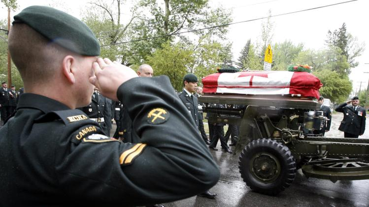 FILE - In this Friday, May 26, 2006 file photo, a member of the Royal Canadian Horse Artillery salutes the coffin of Capt. Nichola Goddard carried on a gun carriage following her funeral service in Calgary, Alberta, Canada. Goddard, Canada's first female combat soldier killed in battle, died by enemy fire in Afghanistan on May 17, 2006. For a nation already divided about participating in the American-led Afghanistan war, Goddard's death was a particular shock, and two more Canadian women have since died in combat. But Canada remains in the small group of countries - including Israel, France, Norway, Australia, New Zealand and now the U.S. - that have opened their fighting ranks to female soldiers. (AP Photo/The Canadian Press, Jeff McIntosh)