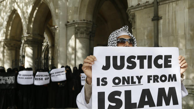 Demonstrators gather outside The Royal Courts of Justice in London Friday, Oct. 5, 2012. Britain's High Court is set to rule Friday afternoon on whether radical cleric Abu Hamza al-Masri and four other terrorist suspects can be extradited to the United States — judgments the government hopes will clear the final hurdle to their removal after years of legal wrangling.. (AP Photo/Kirsty Wigglesworth)