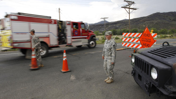 FILE - In this Friday, June 15,2012 file photo Army National Guardsmen Spc. Rachel Cornett, right, and Sgt. Timothy Apodaca let a fire truck pass their road block leading to the Poudre Canyon on  the High Park wildfire west of Fort Collins, Colo. Colorado has some of the tightest restrictions on news media coverage of wildfires, keeping reporters miles away from burn areas and erecting barriers to access to officials in the know and as well as victims. (AP Photo/Ed Andrieski,File)