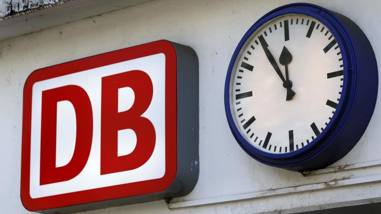 A clock shows the time - five minutes to twelve, next to the logo of German railway company Deutsche Bahn outside the train station in Fulda