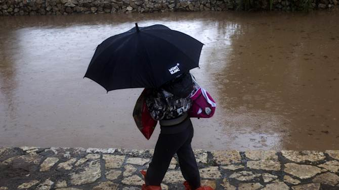 A woman crosses a road next to the blocked and flooded Ayalon freeway in Tel Aviv, Israel,Tuesday, Jan. 8, 2013. Heavy rains flooded Tel Aviv. (AP Photo/Ariel Schalit)