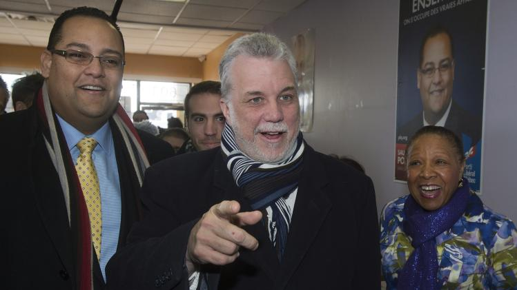Quebec Liberal leader Philippe Couillard, center, speaks to campaign workers while visiting the local riding office, Monday, March 17, 2014, in Laval, Quebec. Quebecers will vote in a provincial election April 7, 2014. (AP Photo/The Canadian Press, Ryan Remiorz)