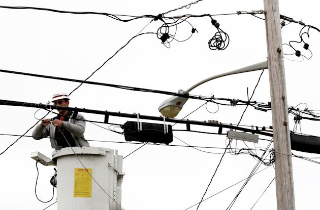 FILE - In this 2006 file photo, a Verizon lineman connects fiber optic cable that will serve a home in North Bellmore, N.Y. Phone companies are losing the high-speed Internet game. In the second quarter, the landline phone industry lost broadband subscribers for the first time, as cable companies continued to pile on new household and small business customers, thanks to the higher speeds they offer in most areas. Verizon Communications Inc., the country's second-largest phone company, has replaced its phone lines with optical fiber in some areas, letting it compete on speed with cable. But expanding service is expensive, so Verizon has stopped adding new areas to its FiOS build-out. (AP Photo/Mark Lennihan, File)