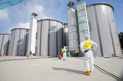 A worker wearing a protective suit and a mask looks up welding storage tanks for radioactive water, under construction in the J1 area at the Tokyo Electric Power Co's tsunami-crippled Fukushima Daiich