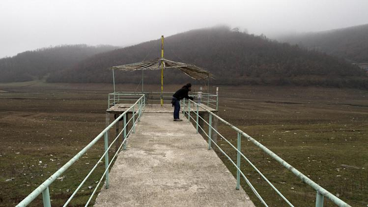 A visitor looks at the dry bed of the Batllava artificial lake from a pier in northern Kosovo on Wednesday, Jan. 8, 2014, after record low water levels threatened to leave hundreds of thousands of people without water supply. Authorities have reduced water supplies for hundreds of thousands of people after an unusually dry winter season. (AP Photo/Visar Kryeziu)