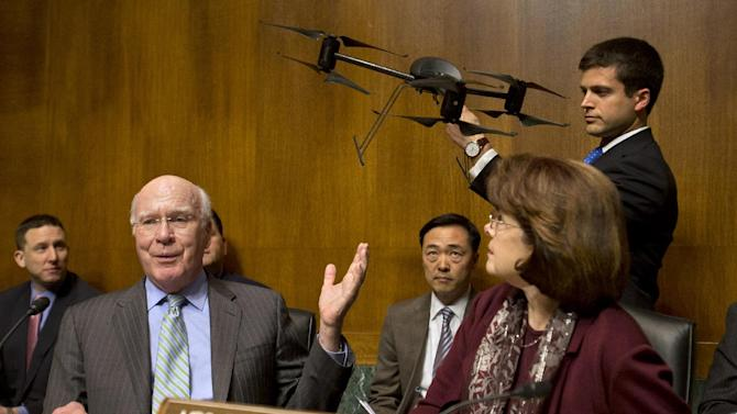 Senate Judiciary Committee Chairman Sen. Patrick Leahy, D-Vt., left, gestures to an example of a drone held by a staff member, on Capitol Hill in Washington, Wednesday March 20, 2013, during the committee's hearing to examine the future of drones in America, focusing on law enforcement and privacy considerations. At right is Sen. Dianne Feinstein, D-Calif. (AP Photo/Jacquelyn Martin)
