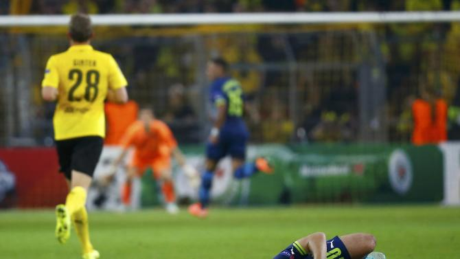 Arsenal's Wilshere lies on the pitch in Champions League soccer match against Borussia Dortmund in Dortmund