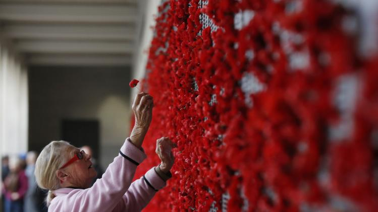Ada Marchant places a poppy flower for her two uncles who died in France during World War I, at the Australian National War Memorial in Canberra