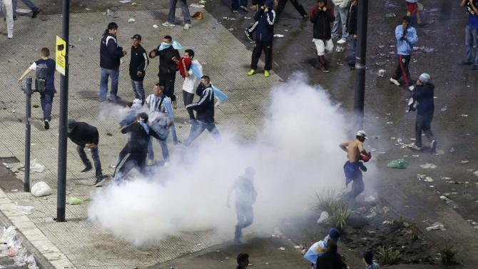 Argentina's fans run from police firing tear gas after Argentina lost to Germany in their 2014 World Cup final soccer match in Brazil, at a public square viewing area in Buenos Aires