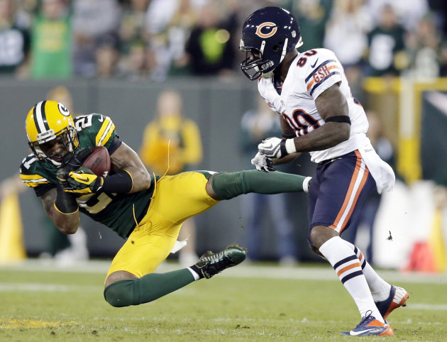 FILE - In this Sept. 13, 2012, file photom, Green Bay Packers' Charles Woodson intercepts a pass in front of Chicago Bears' Earl Bennett (80) during the second half of an NFL football game in Green Ba