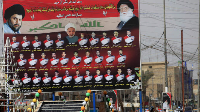 """In this Sunday, Feb. 24, 2013 photo, Iraqi women walk past a billboard showing Shiite religious leaders and Shiite's who were killed during a fight between US troops and al-Mahdi Army militia in the Jihad neighborhood of west Baghdad, Iraq. The fliers claiming to be from a new Iranian-linked Shiite militant group began turning up last week in front of Iraqi Sunni households bearing a chilling message: Get out now or face """"great agony"""" soon.   (AP Photo/ Karim Kadim)"""