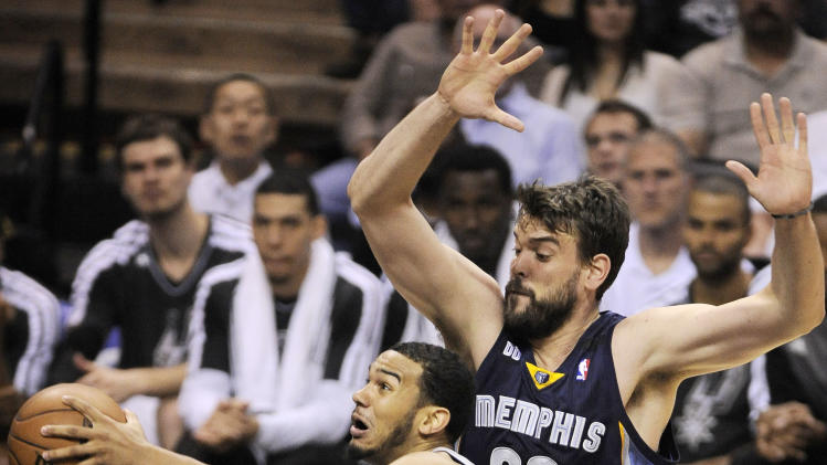 San Antonio Spurs' Cory Joseph, left, drives between Memphis Grizzlies' Marc Gasol, top, of Spain, and Mike Conley during the first half of Game 1 of the Western Conference final NBA basketball playoff series, Sunday, May 19, 2013, in San Antonio. (AP Photo/Darren Abate)