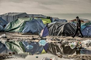"A man walks past tents on November 5, 2015 in the ""Jungle"" …"