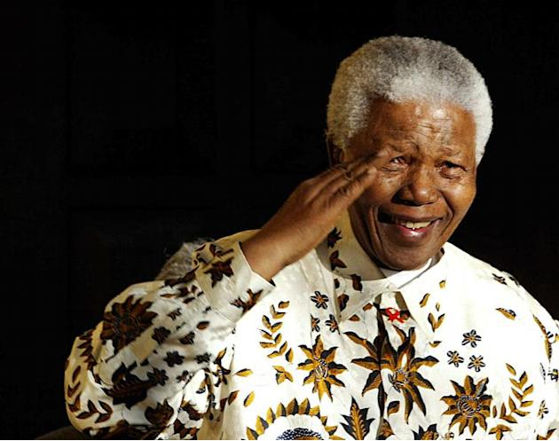 Nelson Mandela salutes the South African military health service band that played a specially composed march on his 85th birthday, on July 18, 2003