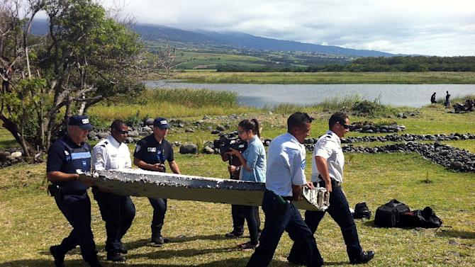Police carry a piece of debris from an unidentified aircraft found on the Indian Ocean island of La Reunion, on July 29, 2015