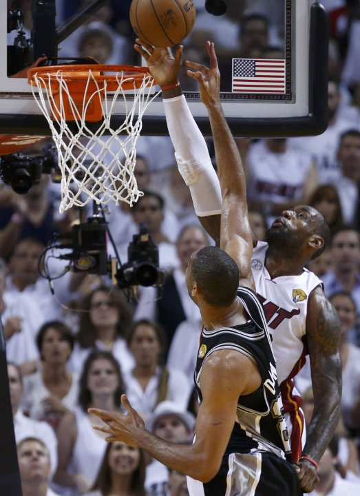 Miami Heat's James blocks a shot by Spurs' Duncan during the fourth quarter in Game 6 of their NBA Finals basketball playoff in Miami