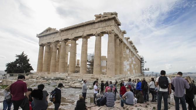 Tourists stand in front of the Parthenon Temple at the archaeological site of the Acropolis Hill in Athens