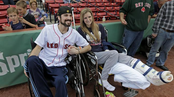 """In this Thursday, May 23, 2013 photo, Boston Marathon bombing survivor Pete DiMartino, of Rochester, N.Y., and his girlfriend, Rebekah Gregory, hold hands prior to DiMartino throwing out the ceremonial first pitch before a Red Sox game at Fenway Park in Boston. DiMartino and Gregory were injured in an explosion near the finish line of the Boston Marathon. """"I don't want anybody feeling sorry for me,"""" he said. """"... I want people to see that this has made me a better person and I want people to become better people through what they see through me."""" (AP Photo/Charles Krupa)"""
