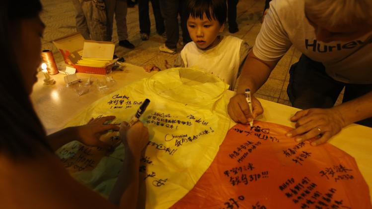 "Malaysian ethnic Chinese write well wishes on ""kongming"" lanterns during candlelight vigil for the passengers of Malaysia Airlines MH370 near Independence Square in Kuala Lumpur"