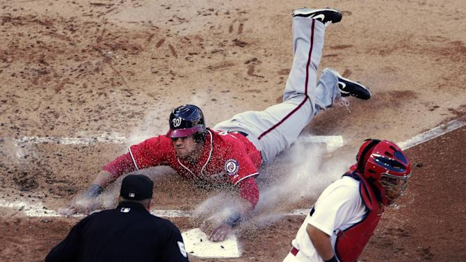 Washington Nationals' Ian Desmond, top, slides home past St. Louis Cardinals catcher Yadier Molina, bottom right, to score on a single by Jordan Zimmermann during the second inning of Game 2 of the National League division baseball series, Monday, Oct. 8, 2012, in St. Louis. (AP Photo/Charlie Riedel)