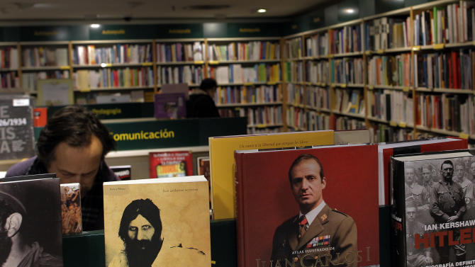 The King of Spain, Juan Carlos' image, centre right, is seen as people look around in a bookstore in Madrid, Spain, Sunday, March 3, 2013. The King of Spain has arrived at a Madrid hospital where he is to undergo surgery for a herniated disc in his lower spine. It will be Juan Carlos' fourth operation in 12 months, and the 12th time he has undergone surgery during his lifetime. (AP Photo/Andres Kudacki)