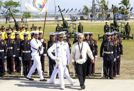 Philippine Defense Secretary Voltaire Gazmin reviews the honor guards upon his arrival to lead the 117th Philippine Navy anniversary held inside the Naval station in Pascual Ledesma, Fort San Felipe, Cavite City, south of Manila
