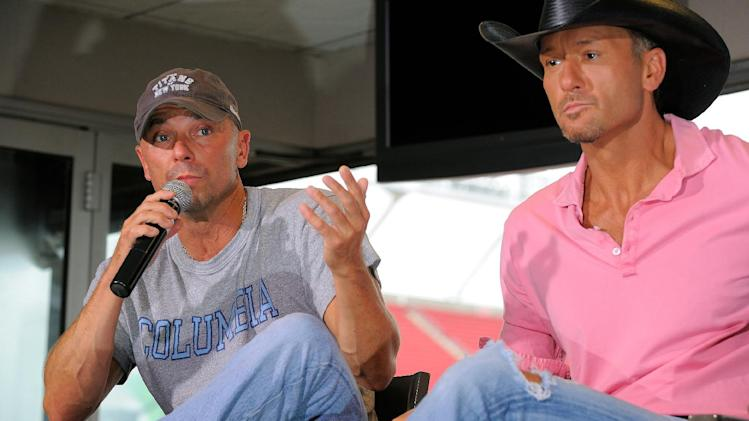 "Country singers Kenny Chesney, left, and Tim McGraw appear at a news conference to promote their ""Brothers of the Sun"" concert tour on Friday June 1, 2012 in Tampa, Fla. The pair will kick off their tour on Saturday night in Tampa, Fla. (Photo by Scott Miller/Invision/AP)"