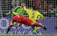 Portugal's Cristiano Ronaldo, foreground, scores the opening goal past Sweden's Martin Olsson, right, and goalkeeper Andreas Isaksson during the World Cup qualifying playoff first leg soccer match between Portugal and Sweden Friday, Nov. 15 2013, at the Luz stadium in Lisbon. (AP Photo/Armando Franca)
