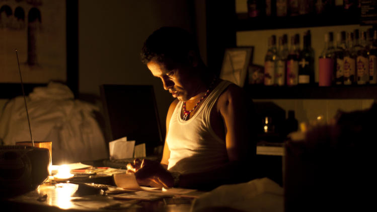 A bartender works on accounts by candle light  during the blackout in Havana, Cuba, Sunday, Sept 9, 2012. Power failed across a large swath of western Cuba on Sunday night, including the capital, Havana, and the popular tourist resort of Varadero, plunging millions of people into darkness. (AP Photo/Ramon Espinosa)