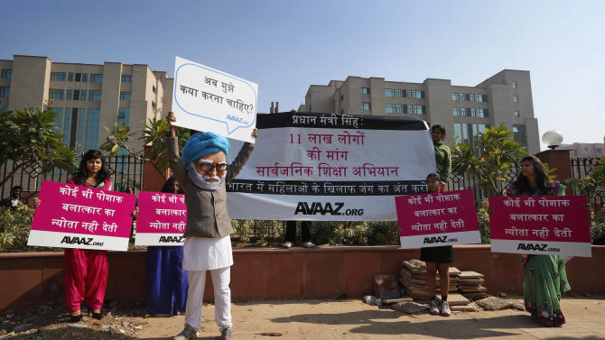 """A man dressed as Indian Prime Minister Manmohan Singh, third left, participates in a protest along with the women, in traditional Indian dresses, outside the court where the accused in a gang rape of a 23-year-old woman are to be tried, in New Delhi, India, Monday, Jan. 21, 2013. Legal proceedings in the fatal gang-rape attack on a student in India's capital were set to begin Monday in a fast-track court for crimes against women that has stirred debate over how best to deliver justice to rape victims. Placard third left reads as, """"What should I do?"""" (AP Photo/Saurabh Das)"""
