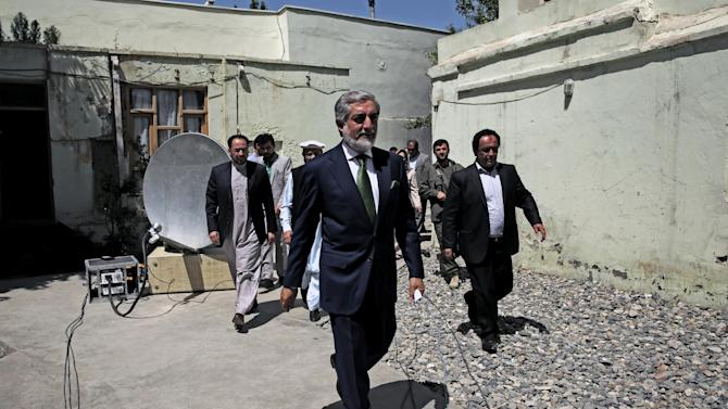 Afghanistan's presidential candidate Abdullah Abdullah, center, arrives for a news conference in Kabul, Afghanistan, Wednesday, June 18, 2014. The front-runner in Afghanistan's runoff presidential election has called for vote counting to stop over fraud claims. (AP Photo/Massoud Hossaini)