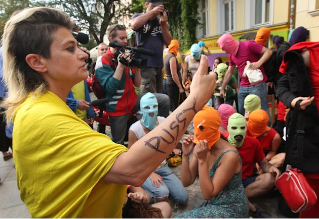 Canadian musician and performance artist Peaches, left, talks to actors wearing masks during the recording of a video of in support of members of the feminist punk group Pussy Riot in Berlin, Germany,
