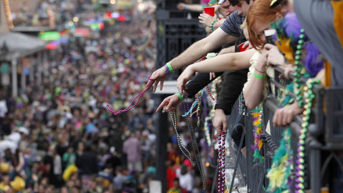 "FILE - In this March 8, 2011 file photo, revelers throw beads from the balcony of the Royal Sonesta Hotel onto crowds on Bourbon Street during Mardi Gras Day festivities in the French Quarter in New Orleans. Mardi Gras is Tuesday, Feb. 12, 2013, but more than a dozen parades roll in the days leading up to Fat Tuesday. The Krewe of Endymion's ""super float"" rolls Saturday night in New Orleans led by pop star Kelly Clarkson. Sunday's Bacchus parade will include more than two dozen child cancer patients from hospitals across the country who will ride with Bacchus celebrity king, actor G.W. Bailey. On Monday, actor Gary Sinise and New Orleans musicians Troy ""Trombone Shorty"" Andrews and Harry Connick Jr. will ride in the Krewe of Orpheus parade.   (AP Photo/Gerald Herbert, file)"