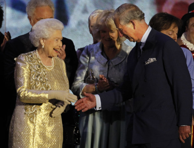 FILE - In this Monday, June 4, 2012 file photo Britain's Queen Elizabeth II shakes the hand of her son Prince Charles at the end of the Queen's Jubilee Concert in front of Buckingham Palace, London. The abdication of Queen Beatrix of the Netherlands sparked some speculation in the British press Tuesday Jan. 29, 2013 about whether Queen Elizabeth II, at 86, might follow suit and step down so her son Charles could become King. But commentators quickly noted that in the past Elizabeth — who seems to be in excellent health — had indicated that she regarded being queen as a job for life. (AP Photo/Joel Ryan, File)