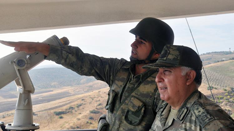 """Turkish Chief of Staff Gen. Necdet Ozel, right, listens to a commander during his tour of the military along the border with Syria in Hatay, Turkey, Tuesday, Oct. 9, 2012. Prime Minister Recep Tayyip Erdogan said Tuesday Turkey was prepared to counter any threats from Syria. """"Every kind of threat to the Turkish territory and the Turkish people will find us standing against it,"""" Erdogan said.(AP Photo/Turkish Military, HO)"""