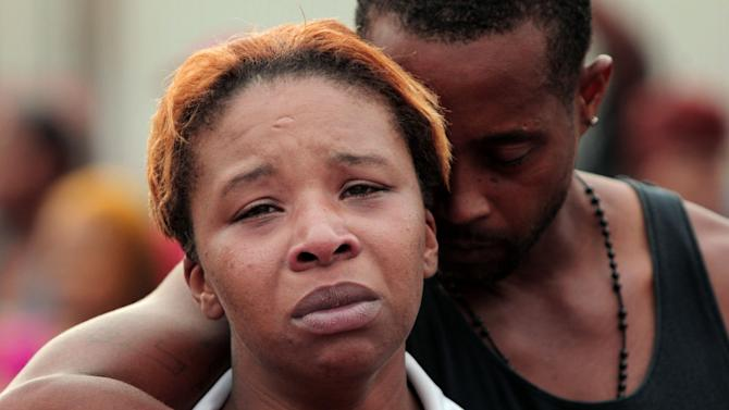Lesley McSpadden, left, is comforted by her husband, Louis Head, after her 18-year-old son, Michael Brown was shot and killed by police in the middle of the street in Ferguson, Mo., near St. Louis on Saturday, Aug. 9, 2014. A spokesman with the St. Louis County Police Department, which is investigating the shooting at the request of the local department, confirmed a Ferguson police officer shot the man. The spokesman didn't give the reason for the shooting. (AP Photo/St. Louis Post-Dispatch, Huy Mach)