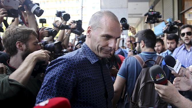 Former Greek Finance Minister Varoufakis is surrounded by media as he leaves the Finance Ministry in Athens