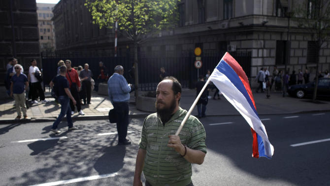 "A man holds a Serbian flag during a demo in Belgrade, Serbia, Monday, April 22, 2013. Thousands of Serb demonstrators, chanting ""Treason, Treason,"" protested on Monday against an agreement to normalize relations with breakaway Kosovo, the potentially landmark deal that could end years of tensions between the Balkan rivals and put them on a path to European Union membership. (AP Photo/ Marko Drobnjakovic)"