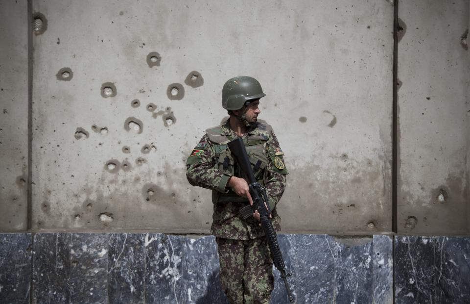 An Afghan Army soldier takes position next to a shrapnel ridden wall at the gate of the Afghan Defense Ministry after a suicide bomber on a bicycle struck outside the ministry, killing at least nine Afghan civilians as U.S. Defense Secretary Chuck Hagel visited Kabul, Afghanistan, Saturday, March 9, 2013.  (AP Photo/Anja Niedringhaus)