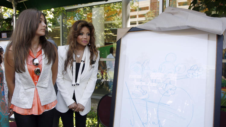 La Toya Jackson, right, stands with Michael Jackson's daughter, Paris Jackson with one of 13 pieces of artwork donated by the pop icon, Michael Jackson, unveiled at the Children's Hospital in Los Angeles,  Monday, August 8,  2011. (AP Photo/Nick Ut)