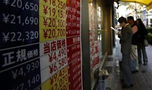 People look at the prices of tickets outside a ticket shop at the Ginza shopping district in Tokyo